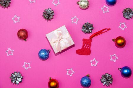 New Year decorations on a bright pink background. Gift box, Christmas cones and stars on a Christmas background.