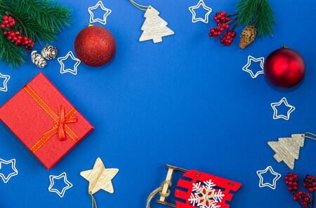 Christmas decorations balls, cones, stars, gift boxes and fir branches on a blue background. Merry Christmas and Happy New Year. Flat lay, top view, layout for recording