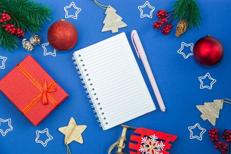 Christmas-tree decorations balls, cones, gift box, Christmas tree branches and notebook for writing on a blue background. The concept of recording Christmas and New Year greetings. Flat lay, top view