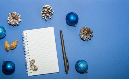 Blank page of notepad for writing with Christmas tree balls and cones on a blue background. The concept of recording Christmas and New Year greetings. Flat lay, top view Фото со стока