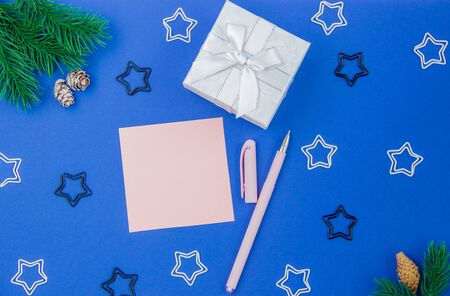 Pink sheet for writing on a festive Christmas background with gift box, spruce branch, cones and stars. New Year greetings concept. Flat lay, top view, layout for recording