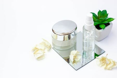Cosmetic bottles with serum, gel, face cream on a mirror a white background with a flower. Skin cosmetics, minimalism Фото со стока