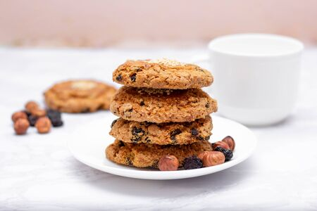 Fresh oatmeal friable cookies on a plate with nuts and raisins. The concept of a delicious and healthy breakfast Фото со стока