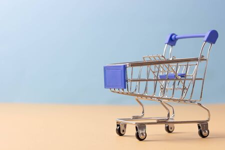 Empty shopping trolley. The concept of going to the store for shopping, buying goods without leaving home Archivio Fotografico