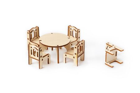Toy miniature wooden furniture set stands on a white background. Dining table and four chairs, one chair fell. Furniture for dolls and dollhouse.