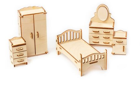 Toy miniature wooden bedroom furniture stands on a white background. Bed, wardrobe, bedside table and chest of drawers. Furniture for dolls and dollhouse. 版權商用圖片