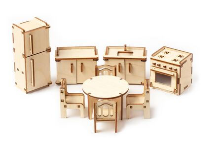 Toy miniature wooden kitchen furniture stands on a white background. Refrigerator, gas stove, sink and dining table with chairs. Furniture for dolls and dollhouse. 版權商用圖片