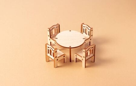A toy miniature wooden furniture set stands on a beige background. Dining table and four chairs. Furniture for dolls and dollhouse. 版權商用圖片