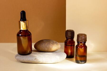 A glass cosmetic bottle with a dropper stands on a stone on a beige background with bright sunlight. Natural cosmetics concept, natural essential oil.