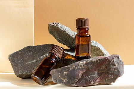 Glass cosmetic bottles stand on a stone on a beige background with bright sunlight. Natural cosmetics concept, natural essential oil