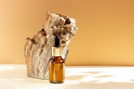 A glass cosmetic bottle with a dropper stands next to a bar of wood on a beige background with bright sunlight. The concept of natural cosmetics, natural essential oil.
