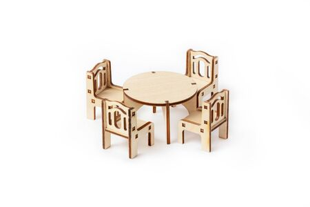A toy miniature wooden furniture set stands on a white background. Dining table and four chairs. Furniture for dolls and dollhouse