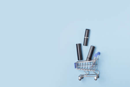 Women's lipsticks and lip glosses in a shopping trolley on a blue background. The concept of buying cosmetics, online shopping