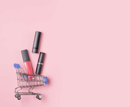Women's lipsticks and lip glosses in a shopping trolley on a pink background. The concept of buying cosmetics, online shopping