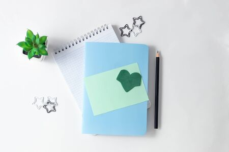 Notepads and empty green sheet for writing and flowers on a white table. Top view, flat lay, copy space, minimalism