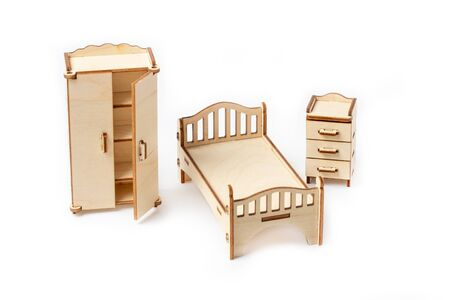 Toy miniature wooden bedroom furniture stands on a white background. Bed, wardrobe, bedside table and chest of drawers. Furniture for dolls and dollhouse. Stock Photo