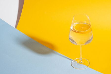 Glass with a summer drink and a slice of orange on a bright yellow background with bright light.