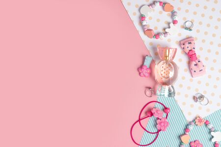 Children's flat lay. Perfume in the form of candy, children's jewelry and hair accessories on a pink background. Accessories for little girls.