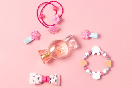 Childrens flat lay. Perfume in the form of candy, childrens jewelry and hair accessories on a pink background. Accessories for little girls Standard-Bild
