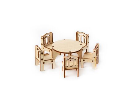 A toy miniature wooden furniture set stands. Dining table and four chairs. Furniture for dolls and dollhouse.