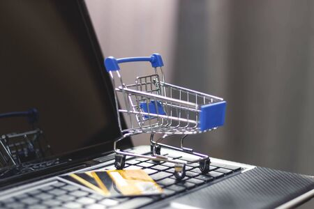 Online shopping with home delivery. Shopping basket on laptop keyboard