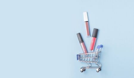 Womens lipsticks and lip glosses in a shopping trolley on a blue background. The concept of buying cosmetics, online shopping.