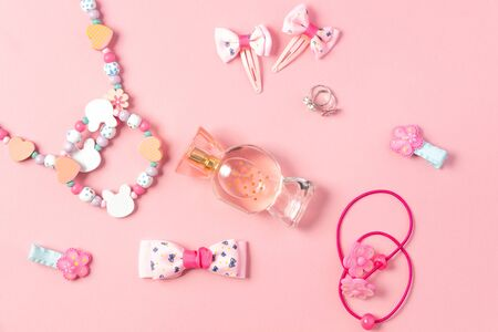Childrens flat lay. Perfume in the form of candy, childrens jewelry and hair accessories on a pink background. Accessories for little girls.
