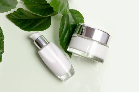 Natural organic cosmetics with green leaves. Blank label for mock branding.