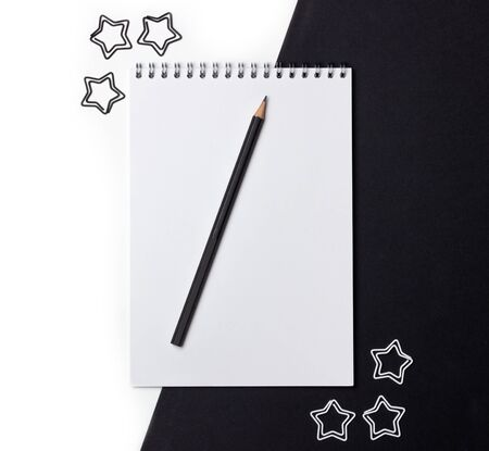 White open blank notebook with black pencil on a black background