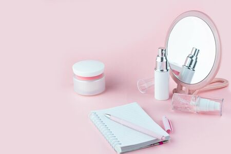 Face care cosmetics. Jars of cream and face serum and notes for writing on a pink background Standard-Bild