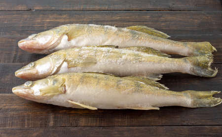Fresh frozen freshwater fish on a dark wooden table. Top view, copy space, minimalist concept.