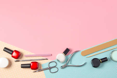 Tools for manicure on a pink and blue background. Nail files, scissors and nail polishes top view. Nail Salon, Beauty Salon.