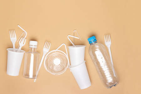 Plastic dishes, bottles, glasses on a white table. Planet pollution.