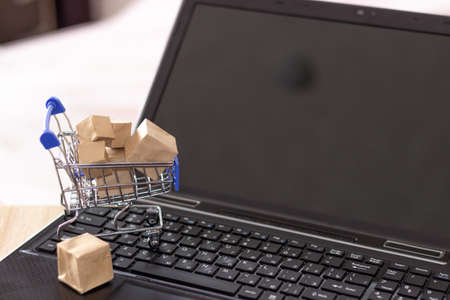 Online shopping with home delivery. Shopping basket and boxes on laptop keyboard