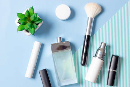 Women's cosmetics and accessories on a blue striped background: perfume, cream, lipstick, makeup brush. Fashion and Beauty Concept. Standard-Bild