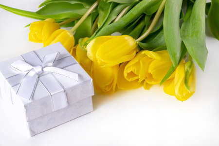 A bouquet of yellow tulips and gift boxes on a white background with place for adding notes. Standard-Bild