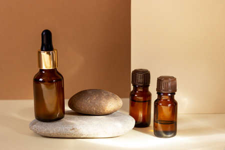 Glass cosmetic bottles with a dropper stand next to a log on a beige background with bright sunlight. The concept of natural cosmetics, natural essential oil Standard-Bild