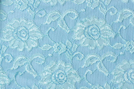 Blue lace texture with flowers on a blue background. Background of blue lace with a floral pattern on a blue background Standard-Bild