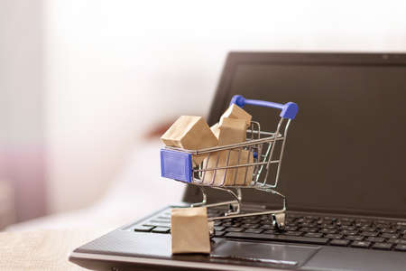 Shopping basket and boxes on laptop keyboard. Online shopping with home delivery
