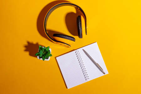 Desktop with yellow wireless headphones and an open notebook on a bright yellow background