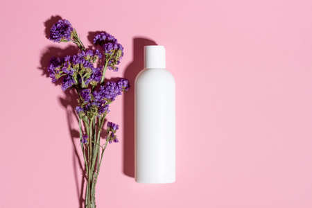 Natural cosmetics in a white bottle top view on a pink background