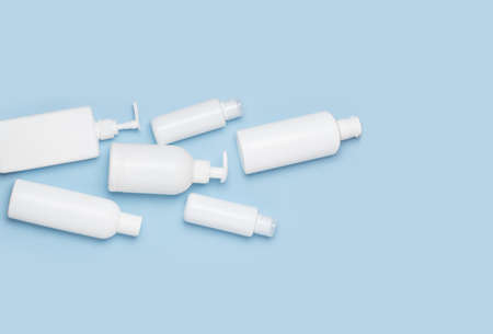 A set of white cosmetic cans for face and body care are in a basket on a blue background. Purchase of cosmetics and hygiene products, home shopping. Standard-Bild
