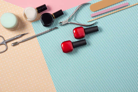 Tools for manicure on a pink and blue background. Nail files, scissors and nail polishes top view. Nail Salon, Beauty Salon