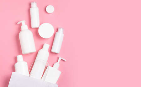 White cosmetic jars on a pink background. Cosmetics for skin care.