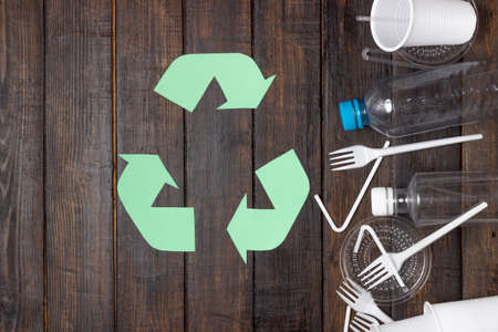 Plastic dishes, bottles, glasses on a white table. Planet pollution