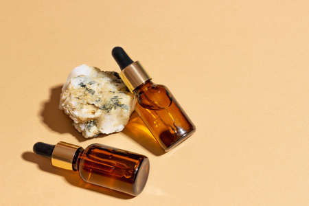 Natural cosmetics in glass bottles with a dropper stand next to a stone on a beige background with bright sunlight. The concept of natural cosmetics, natural essential oil Standard-Bild