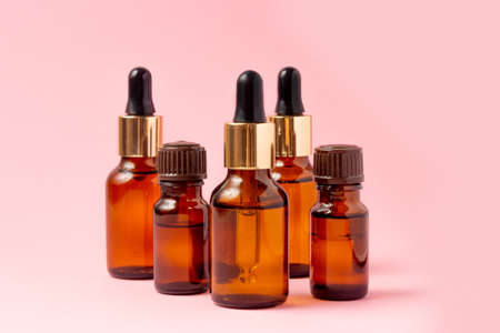 A set of amber bottles for essential oils and cosmetics. Glass bottle on a pink background. Dropper, spray bottle