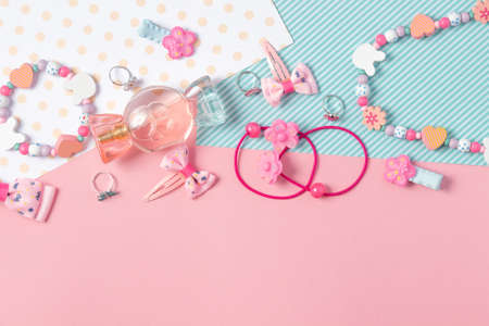 Children's flat lay. Perfume in the form of candy, children's jewelry and hair accessories on a pink background. Accessories for little girls. Standard-Bild
