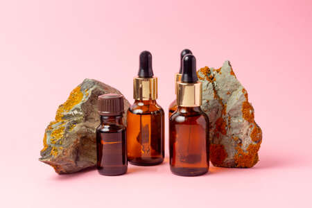 An amber bottle for essential oils and cosmetics stands next to the stone. Glass bottle on a pink background. Dropper, spray bottle. Natural cosmetics concept.