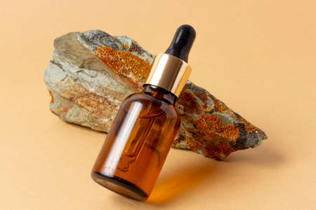 An amber bottle for essential oils and cosmetics stands next to the stone. Glass bottle. Dropper, spray bottle. Natural cosmetics concept.